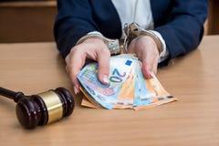 Dient handcuffs in voor steekpenning met euro wordt gearresteerd die stock afbeelding