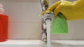 Dient handschoenen in wassen de gootsteen in de badkamerswas stock video