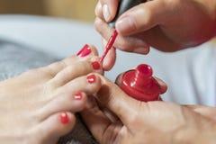 Dient handschoenenzorgen over de spijkers van een vrouwen` s voet in Pedicure, de salonconcept van de manicureschoonheid Spijker  stock afbeeldingen