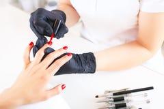 Dient handschoenenzorgen over handenspijkers in De salon van de manicureschoonheid stock foto's