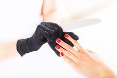 Dient handschoenenzorgen over handenspijkers in De salon van de manicureschoonheid royalty-vrije stock foto's