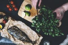 Dient het proces om vissen, peper, peterselie, tomaat, kalk op een knipselraad op in een zwarte houten hoogste mening als achterg stock afbeelding