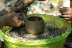 Dient klei in Het wiel van de pottenbakker om een kop van klei te maken royalty-vrije stock fotografie