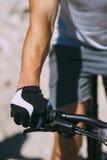 Dient sportenhandschoenen, fiets en wiel in stock afbeelding