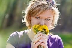 Diente de león del olor de la mujer joven imagen de archivo