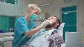 Diente paciente del ` s de la perforación femenina del dentista y mirada a la cámara steadicam metrajes