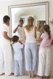 Dientes de cepillado de la familia en espejo del cuarto de baño Fotografía de archivo