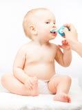 Dientes de cepillado de la madre de su pequeño bebé foto de archivo libre de regalías