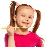 Dientes de cepillado de la muchacha linda con el cepillo de dientes amarillo Imagen de archivo libre de regalías