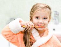 Dientes de cepillado de la niña linda en baño Fotos de archivo libres de regalías