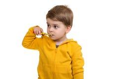 Dientes de cepillado de Little Boy en el fondo blanco imagenes de archivo