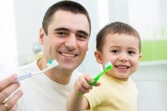 Dientes de cepillado del hijo del padre y del niño en cuarto de baño Foto de archivo libre de regalías