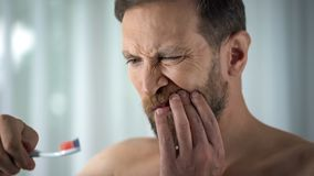 Dientes de cepillado del hombre caucásico y sangre en el cepillo de dientes, cuidado dental, dolor el ver foto de archivo