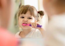 Dientes de cepillado de la muchacha linda del niño y mirada en espejo en cuarto de baño fotografía de archivo