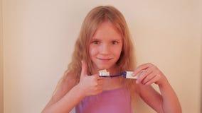 Dientes de cepillado de la pequeña muchacha rubia hermosa, concepto sano almacen de video