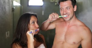 Dientes de cepillado de los pares en cuarto de baño, hombre alegre e higiene sonriente feliz de la mañana de la mujer que hace metrajes
