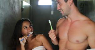 Dientes de cepillado de los pares en el baile del cuarto de baño, el hombre alegre y la higiene sonriente feliz de la mañana de l almacen de metraje de vídeo