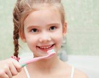 Dientes de cepillado sonrientes de la niña linda Imágenes de archivo libres de regalías