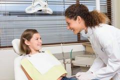 Dientes de examen de las niñas del dentista pediátrico en la silla de los dentistas Foto de archivo libre de regalías