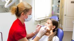 Dientes de examen de los pacientes del dentista de sexo femenino joven con los instrumentos especiales Fotografía de archivo libre de regalías