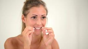 Dientes de la limpieza con seda dental almacen de metraje de vídeo