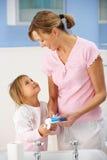 Dientes de la limpieza de la madre y de la hija en cuarto de baño foto de archivo