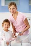 Dientes de la limpieza de la madre y de la hija en cuarto de baño fotos de archivo libres de regalías