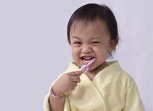 Dientes de la limpieza de la muchacha del niño con el cepillo de dientes Fotos de archivo libres de regalías