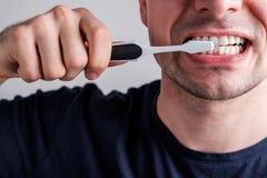 Dientes de la limpieza del hombre con el cepillo de dientes foto de archivo