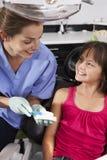 Dientes del cepillo de Demonstrating How To del dentista foto de archivo