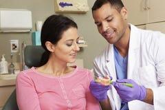 Dientes del cepillo de Demonstrating How To del dentista al paciente femenino fotografía de archivo libre de regalías