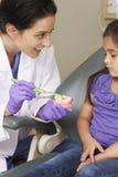 Dientes del cepillo de Demonstrating How To del dentista al paciente femenino joven foto de archivo
