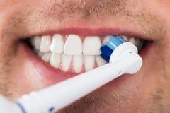 Dientes del hombre con el cepillo de dientes eléctrico Imágenes de archivo libres de regalías