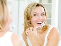 Dientes felices de la limpieza de la mujer con el cepillo de dientes Imagen de archivo