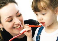 Dientes que aplican con brocha de la madre y de la hija foto de archivo