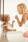 Dientes que aplican con brocha de la madre y de la hija en cuarto de baño Imagen de archivo libre de regalías