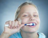 Dientes que aplican con brocha de la muchacha. Imagenes de archivo