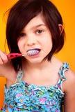 dientes que aplican con brocha de la muchacha de 7 años Foto de archivo libre de regalías