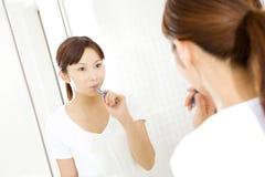 Dientes que aplican con brocha de la mujer japonesa Foto de archivo