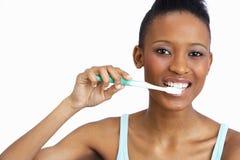 Dientes que aplican con brocha de la mujer joven en estudio Imagen de archivo libre de regalías