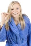 Dientes que aplican con brocha de la mujer rubia joven Imagen de archivo libre de regalías