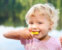 Dientes que aplican con brocha de la niña Imagenes de archivo