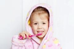 Dientes que aplican con brocha de la niña Foto de archivo libre de regalías