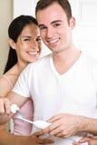 Dientes que aplican con brocha de los pares en el cuarto de baño Fotografía de archivo libre de regalías