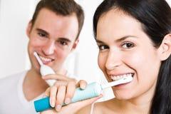 Dientes que aplican con brocha de los pares en el cuarto de baño Foto de archivo libre de regalías