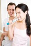 Dientes que aplican con brocha de los pares en el cuarto de baño Imagen de archivo
