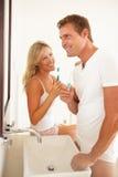 Dientes que aplican con brocha de los pares jovenes en cuarto de baño Imagen de archivo