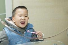 Dientes que aplican con brocha del muchacho Foto de archivo
