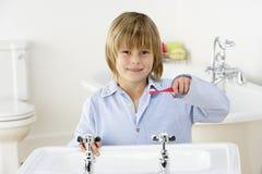 Dientes que aplican con brocha del muchacho joven en el fregadero Foto de archivo