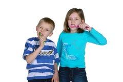 Dientes que aplican con brocha del muchacho y de la muchacha Imágenes de archivo libres de regalías